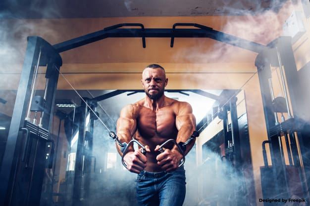 Strong body builder using the cable crossover