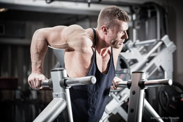 man doing dips in the gym